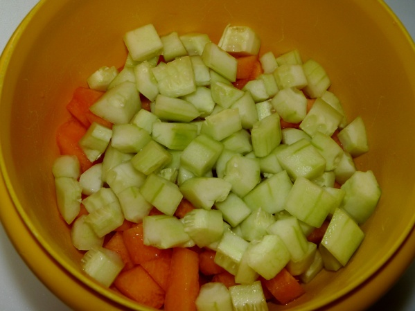 Dice cantaloupe and cucumbers
