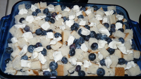 Then spread the rest of the bread cubes, blueberries, and cream cheese