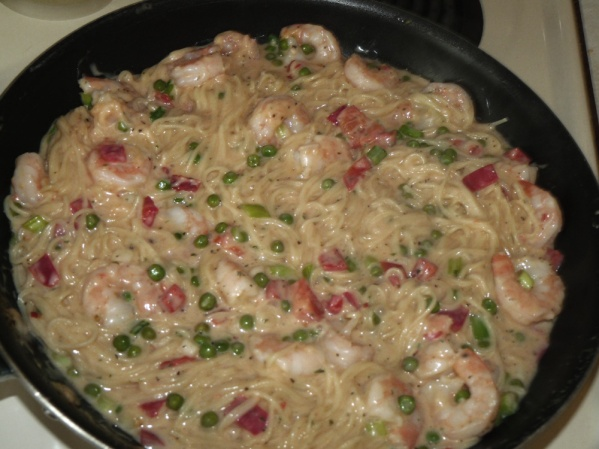 Stir the pasta into the shrimp Alfredo sauce until it absorbs some of the sauce