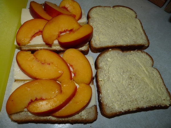 Butter insides of bread slices and layer with cheese, then sliced peaches