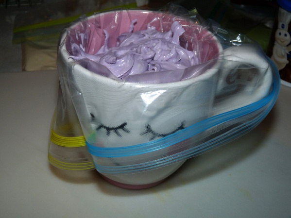 Put the bag into a cup and scoop the frosting into the bag neatly