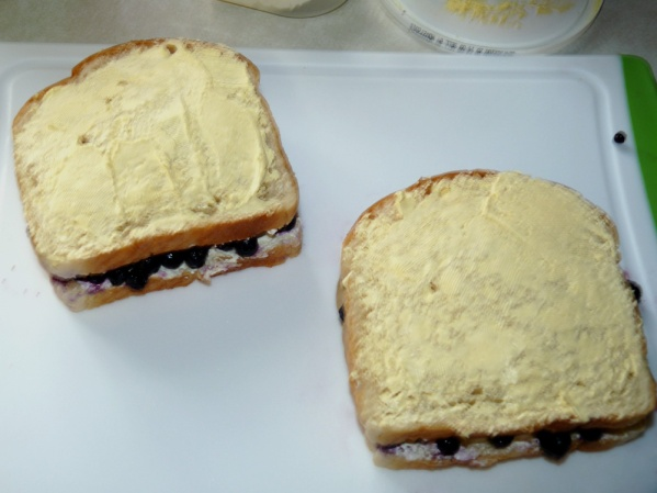 Lay the second slice of bread over the berries and butter the top