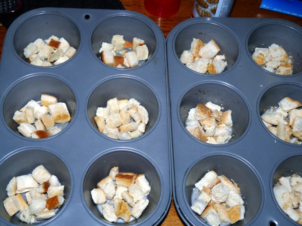 Grease or spray pans and add layer of bread cubes