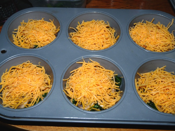 Layer mushrooms, spinach and cheddar in the muffin cups
