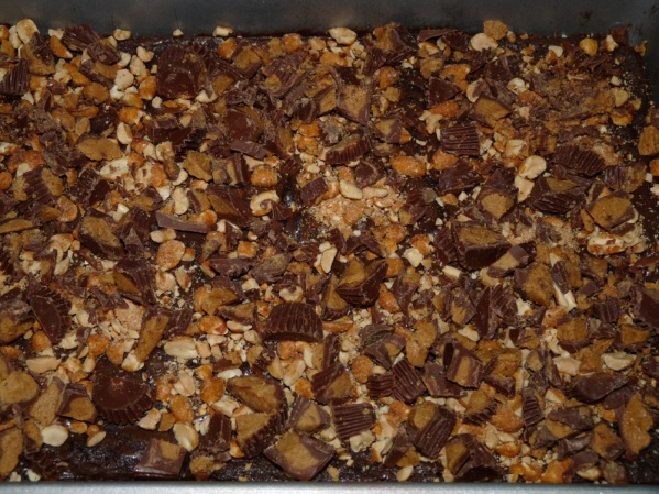 Spread chopped PB cups and chopped nuts over the hot brownies