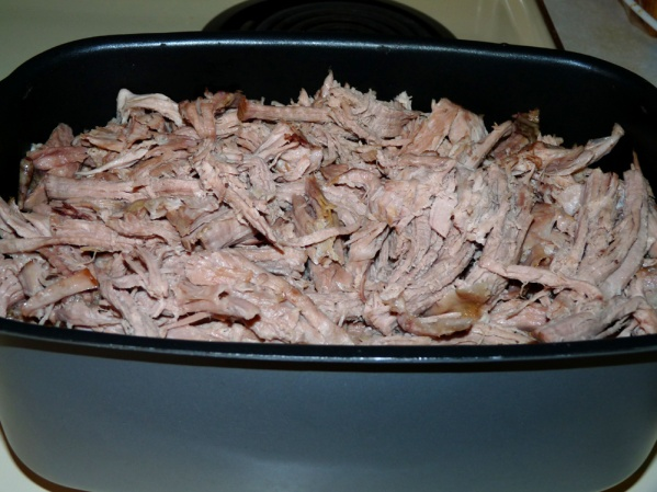 Add 2/3 of the pulled pork (about 10 lbs) to the sauce and simmer for one hour