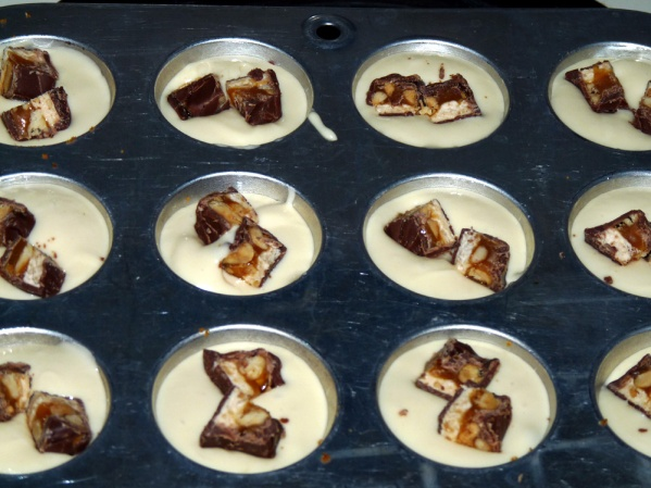 Scoop batter into cups and add 1/4 a small Snickers bar
