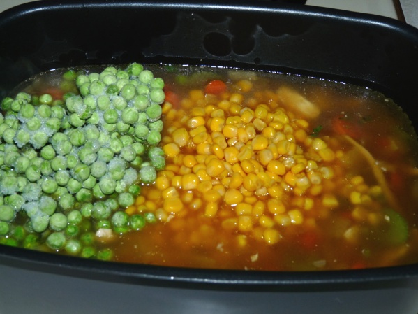 Add broth, turkey, a can of corn and a cup of frozen peas