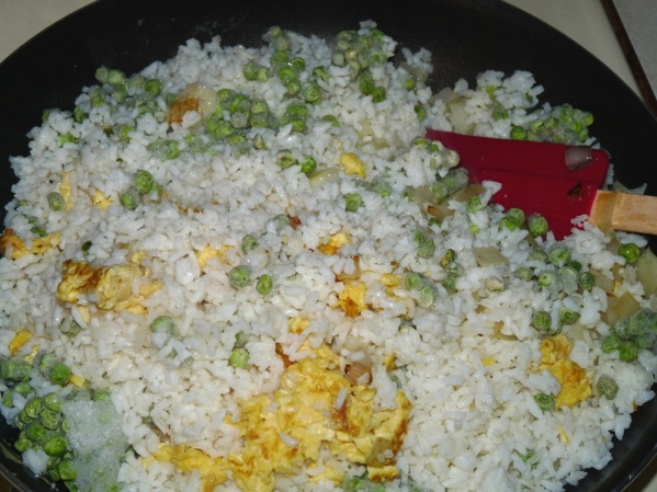 Add rice and frozen peas to the skillet