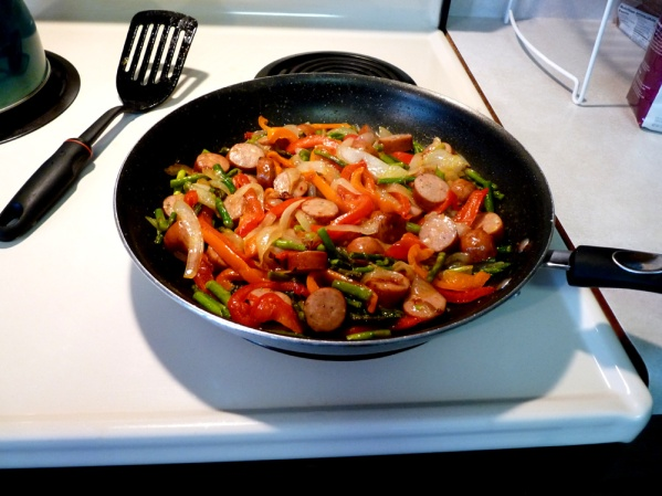 Stir fry sliced sausages, peppers and onions