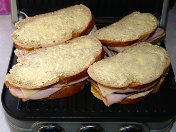 Butter tops and bottoms and place on Panini press