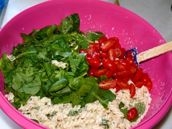 Stir in spinach and tomatoes after pasta has cooled