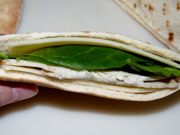 Tuck cheese against each side, then spinach and turkey between the cheese slices