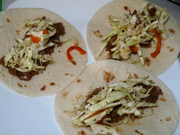 Heat tortillas and layer meat and slaw down the middle of each