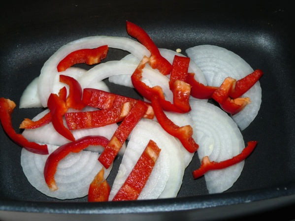 Slice peppers and onions and layer half on the bottom of the crockpot