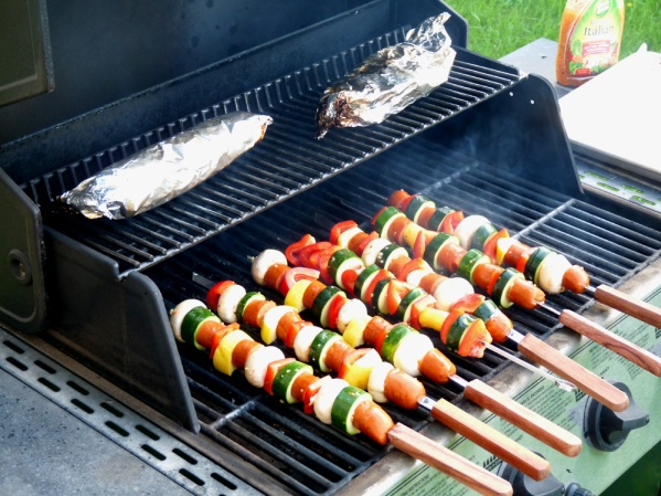 Skewers on the grill with potato packets on the upper rack