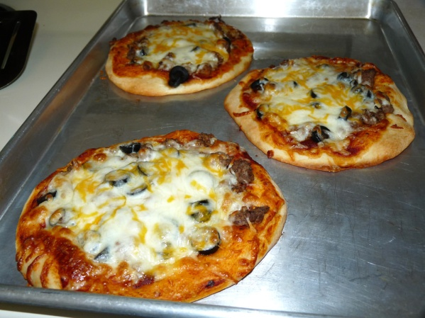 Hunter's first pan of ground beef and black olive pizzas