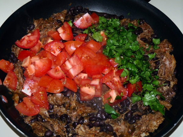 In a skillet over medium heat, add shredded pork, black beans, tomatoes and cilantro