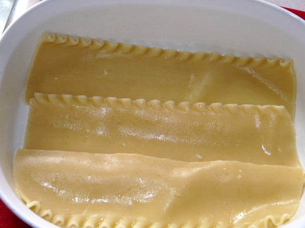 Spray baking dish and place one layer of noodles