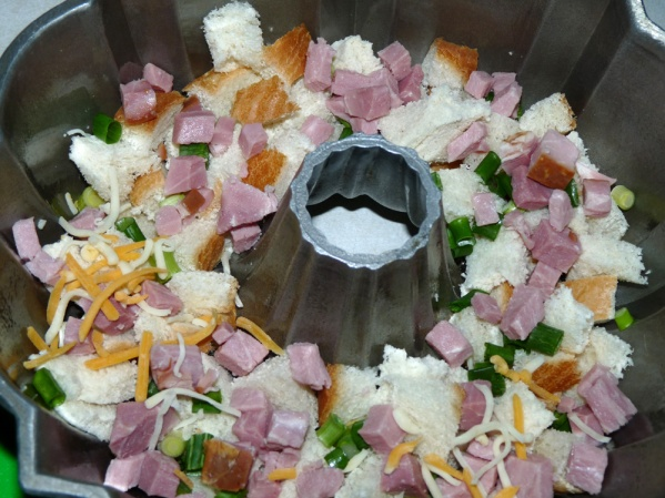 Spray or grease bundt pan well. Layer half of the bread cubes, followed by layers of ham, green onions and cheese