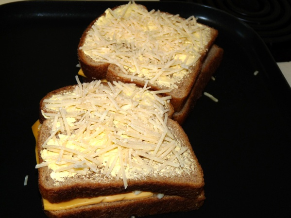 Add favorite cheeses, place top slice of bread and butter.  Sprinkle with Parmesan