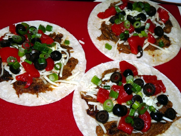 Layer cheese, pork, peppers, green onions and tomatoes on the tortillas