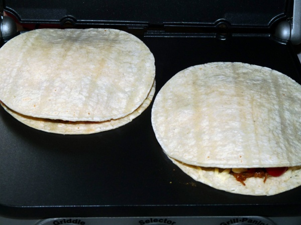 Cover with second tortilla and place on heated panini griddle