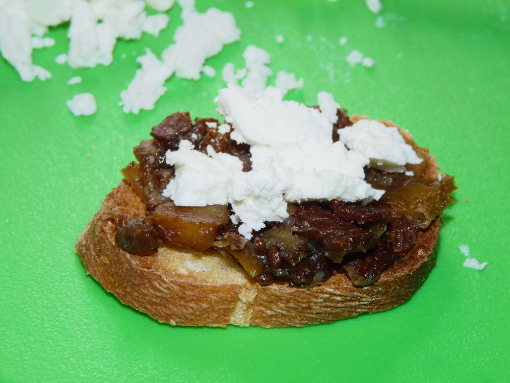 Spread jam on crostini then sprinkle with crumbled goat cheese