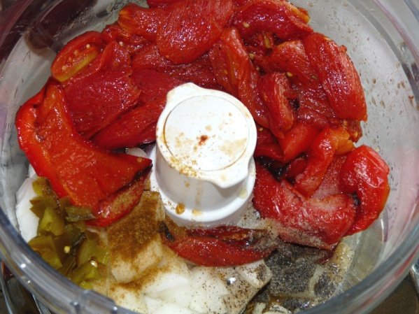 Place tomatoes and pepper into the bowl of a food processor with onions, garlic, jalapenos, sugar and seasonings