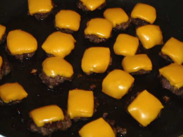 Cut cheese slices into smaller squares and place on burgers and let melt