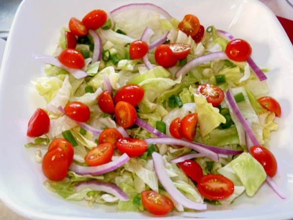 I salad bowls layer lettuce, cherry tomatoes, sliced red onions and green onions