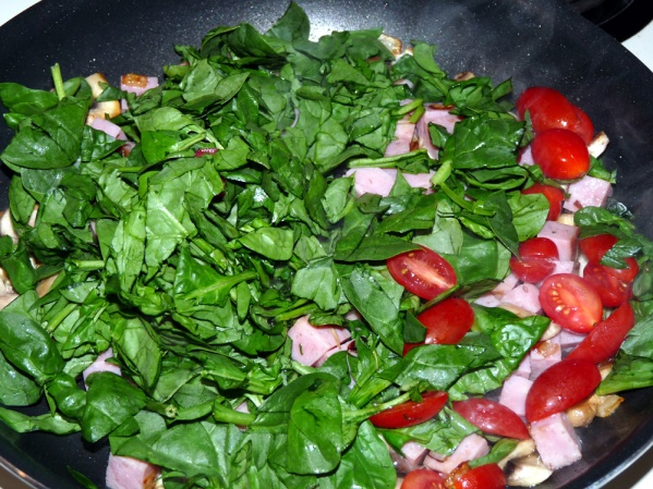 Add chopped spinach and halved cherry tomatoes