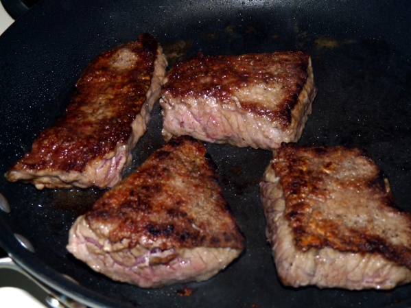 Heat skillet to medium high with a drizzle of oil. Sear steaks on first side until nicely browned. Turn and sear on the second side.