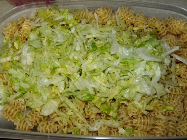Add pasta to a large container or bowl. Add shredded lettuce