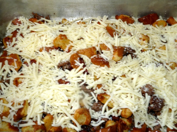Layer half of the bread and meat mixture into a sprayed 9x13-in pan. Top with 1 1/2 cups of cheese. Top with remaining meat mixture and remaining cheese.