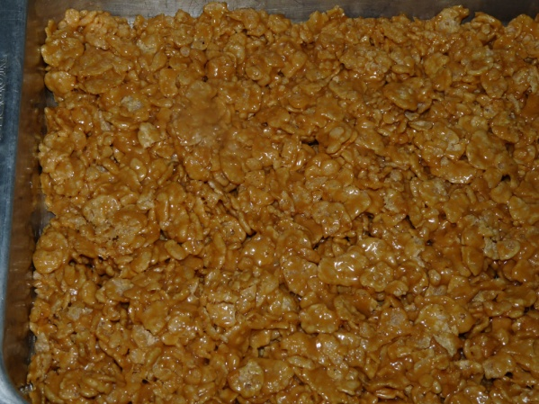 Spread cereal mixture evenly into the prepared 9x13-in pan, leaving the top flattened for the frosting.