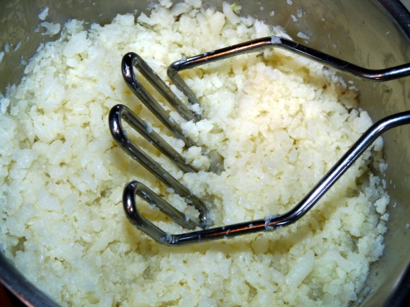 Use a food processor or potato masher to reduce cauliflower to rice sized pieces