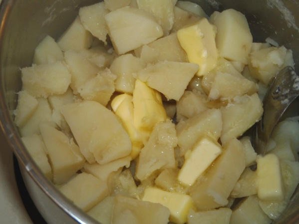 Boil potatoes until fork tender. Place butter pieces and seasonings in saucepan