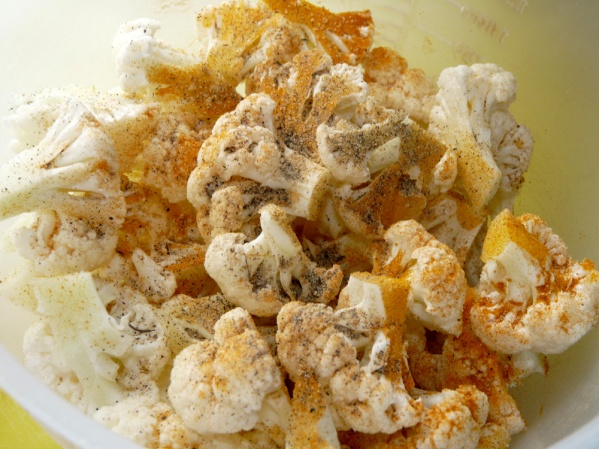 Cut cauliflower into smaller pieces and add to bowl with turmeric, salt and pepper. Add oil and toss or mix until all pieces are coated