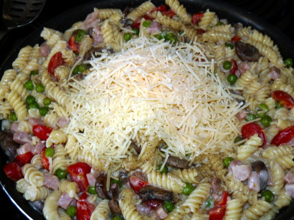 Drain pasta and reserve several cups of pasta water. Stir pasta into skillet along with shredded Parmesan