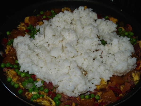 Using your hand, work oil into the cold rice then add to the skillet.