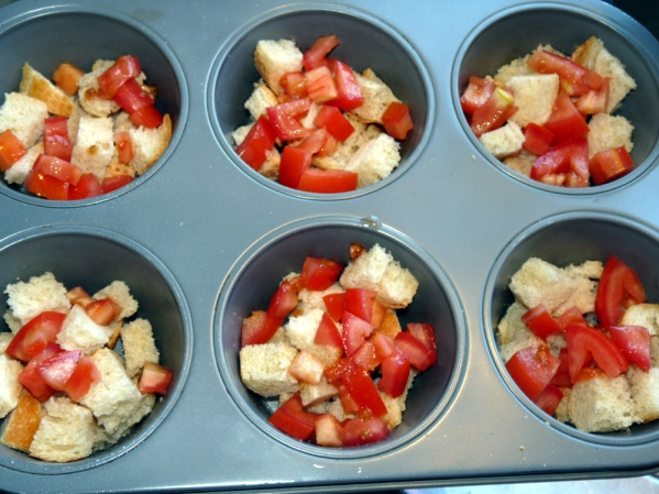 Spray or grease 12 jumbo muffin cups and place 8-9 cubes of bread in each cup. Divide browned peppers among the cups.