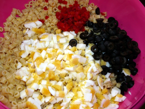 Add pasta, diced eggs, black olives and drained pimentos to a large bowl