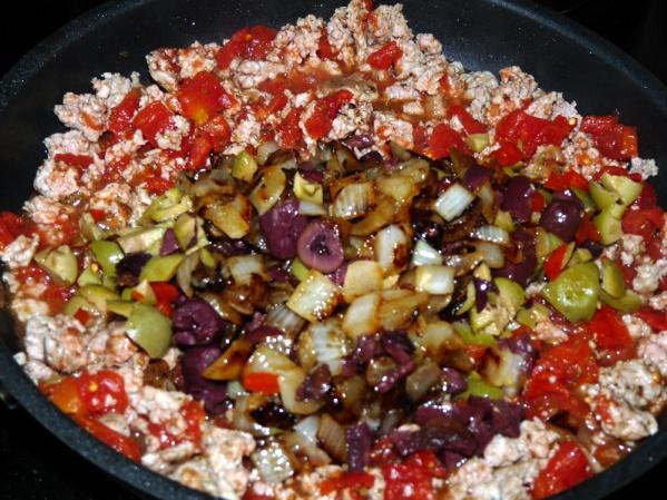 Add garlic powder, oregano, basil, onions and olives.