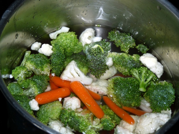 Add smaller carrots, broccoli and cauliflower to saucepan. Cover with water and add salt.