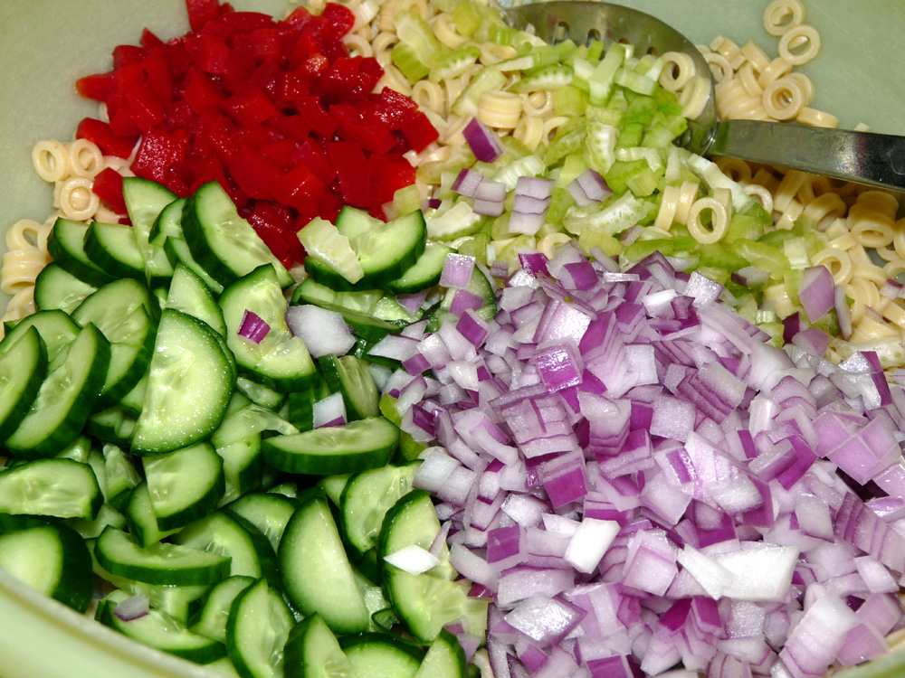 Place pasta, cucumbers, celery, peppers and red onion in a large bowl.