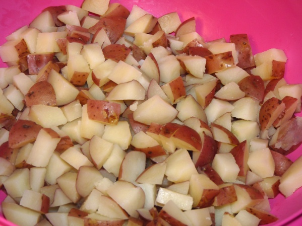 "Scrub potatoes and cut into 3/4"" cubes. Boil in salted water until fork tender. Drain and cool."