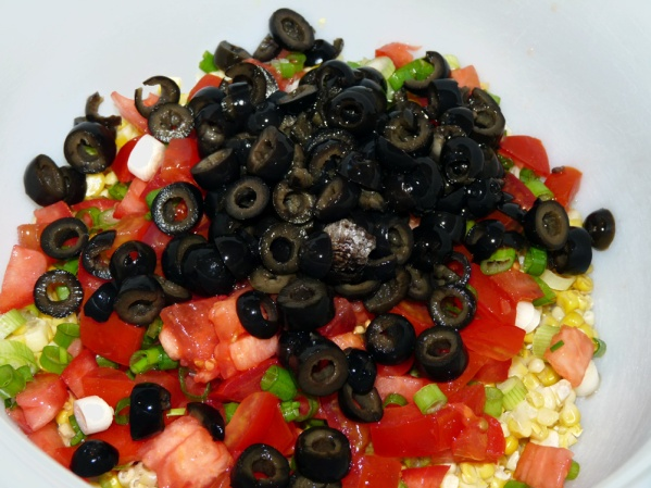 Drain can of sliced black olives and add to bowl.