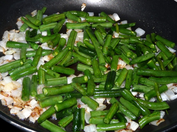 Sauté onions in a drizzle of oil until they begin to turn translucent. Add green beans and sauté another 3-4 minutes, until they can be cut easily with the edge of a spatula.