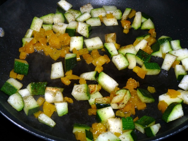In a nonstick skillet heat a drizzle of oil. Add diced zucchini and peppers. Cook until zucchini is lightly browned.